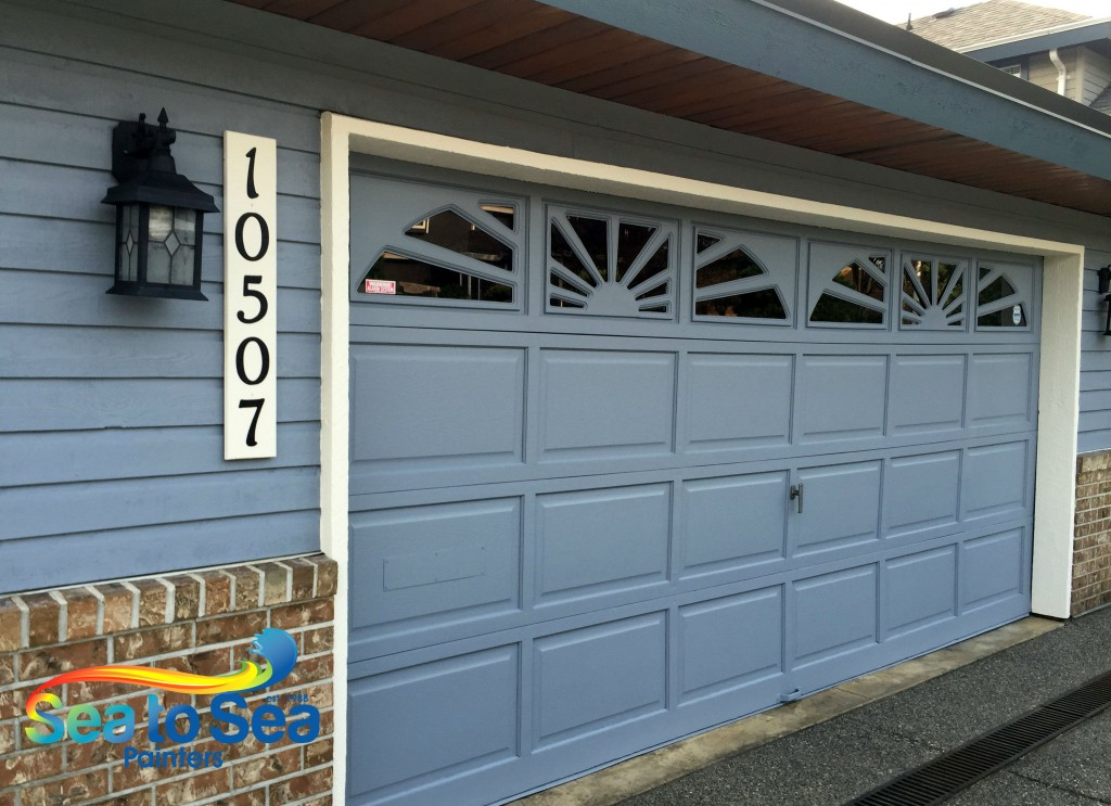 Solid colour garage door with sunburst windows.  Painted with Diamond.